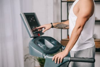 man pushing buttons on the control panel to start jogging