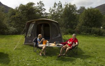 a couple taking breakfast outside their tent