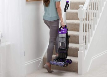 a woman carrying a vacuum upstairs