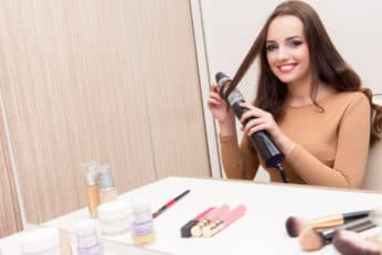 young woman using hair styler