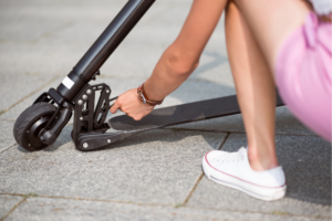 young woman checking e-scooter