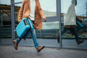 man running with luggage in hand